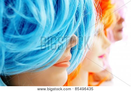 closeup of some wigs of different colors on mannequin heads