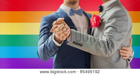 people, homosexuality, same-sex marriage and love concept - close up of happy male gay couple holding hands and dancing on wedding over rainbow flag background