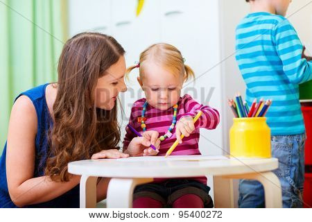 Young mother and her daughter drawing together. Also perfect for kindergarten daycare context.