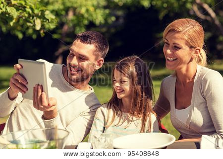 family, happiness, generation, home and people concept - happy family sitting at table and taking selfie with tablet pc computer outdoors