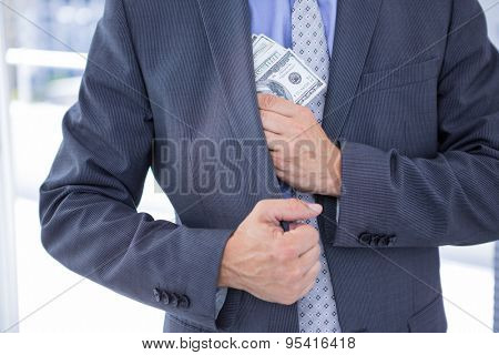 Dodgy businessman pocketing a bundle of dollar bills