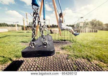 Empty playground swing with children playing in the background concept for child protection, abduction or loneliness
