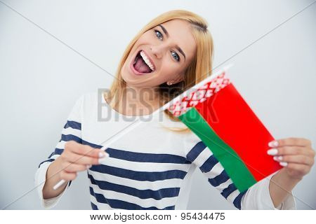 Cheerful young girl holding Belarussian flag over gray background