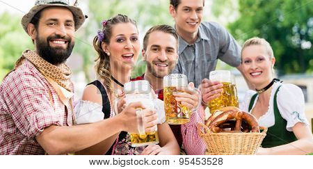 Friends in Bavarian beer garden drinking in summer