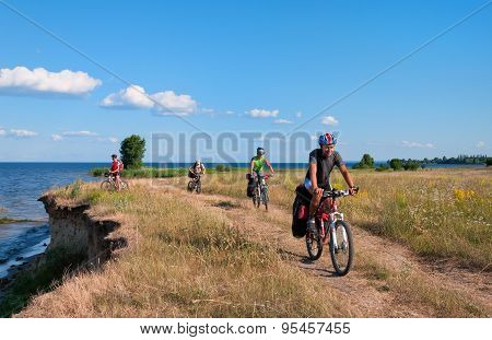 Group of tourists  mountain bike ride on dirt road.