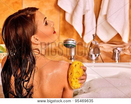 Young woman with bare back take bubble  bath.