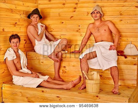Group people of men in  hat  relaxing at sauna on stag-party.