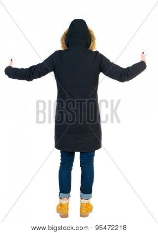 Back view of Beautiful woman in parka looking at wall and Holds  hand up.   tall girl in a black warm jacket with a hood placed over the head spread his arms. a hood commended hands to the sky.