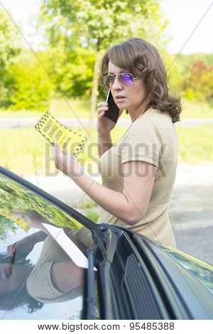 Suprised woman looking on parking ticket placed under windshield wiper and talking on the mobile phone