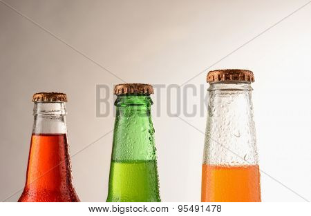 Three different soda bottles covered with condensation. Horizontal format with a warm light to dark background. Sodas are; Strawberry, orange, and lemon lime.