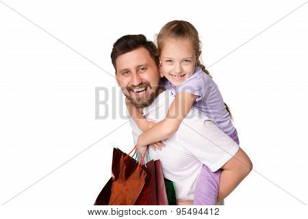 Happy father and daughter with shopping bags standing at studio