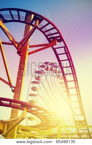 Vintage stylized roller coaster in amusement park at sunset. poster