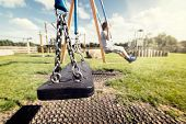 Empty playground swing with children playing in the background concept for child protection, abduction or loneliness poster