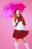 Cute smiling teen girl in school plaid skirt and white blouse posing over pink background. Anime style.  poster