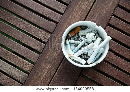 top view of ashtrays, cigarette butts, garbage cleaning on a wooden table.