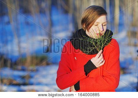 Portrait of beautiful woman with closed eyes in a red coat with a green twig in the hands cold weather in a snowy forest.