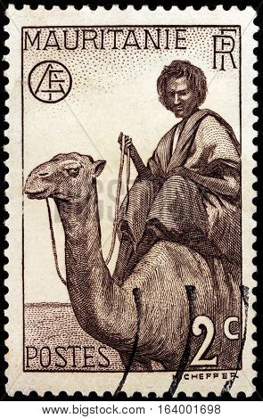 LUGA RUSSIA - NOVEMBER 29 2016: A stamp printed by MAURITANIA shows Nomand Man on Dromedary against native desert landscape circa 1938