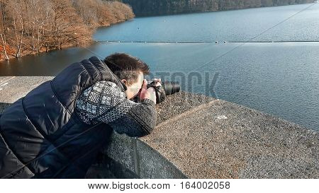 Photographer with camera making a panoramic photo of a dam.