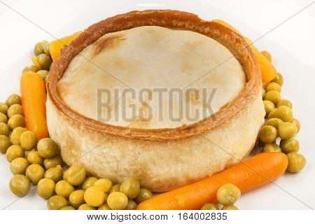 fresh baked scottish pie with carrot and pea on a plate