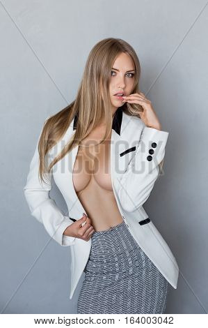 Portrait of gorgeous young caucasian attractive sexy business woman or secretary wearing white suit with decollete big breast aganst gray wall background