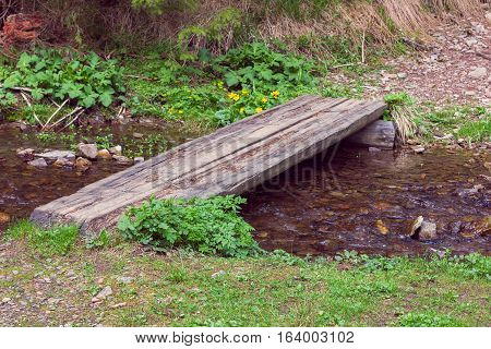 wooden crossbar over a stream in the woods