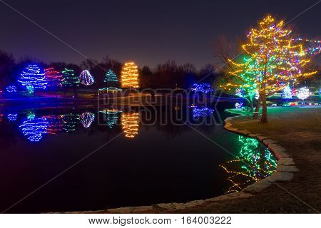 View of a lake with many Christmas decorated lights on trees around the lake.