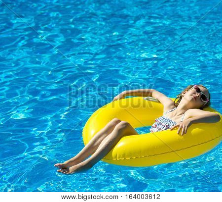 Little Girl With Inflatable Rubber Ring Relaxing In Swimming Pool. Place For Text.