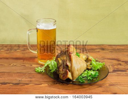 Baked ham hock with lettuce and parsley on a glass dish and glass of lager beer on an old wooden surface