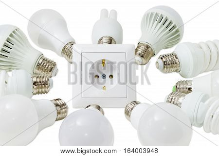 Several different domestic light emitting diode lamps and compact fluorescent lamps with a sized E27 male screw base around the power socket closeup on a light background