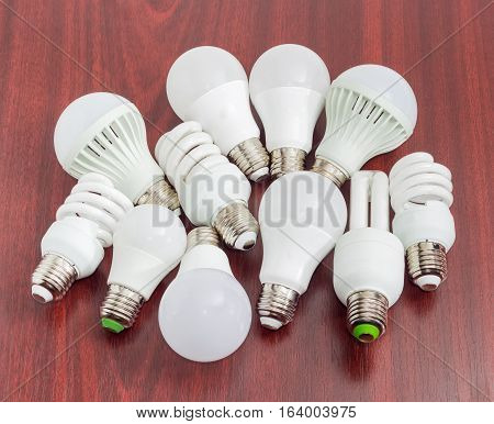 Several different domestic light emitting diode lamps and compact fluorescent lamps with a sized E27 male screw base on a dark wooden surface