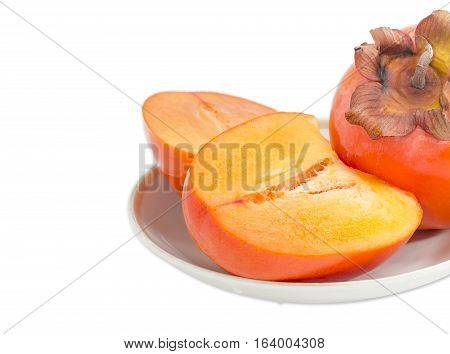 Fragment of whole ripe fresh persimmon and cut in half of a persimmon on saucer closeup on a light background
