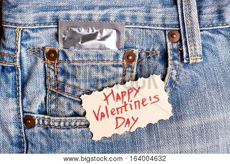 Valentine's Day card and condom. Greeting card on denim. Be safe while celebrate.