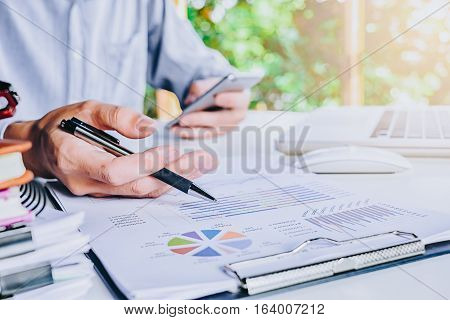 Business man discussing the analysis charts or graphs on modern White office desk table and using smart phone.Business concept.