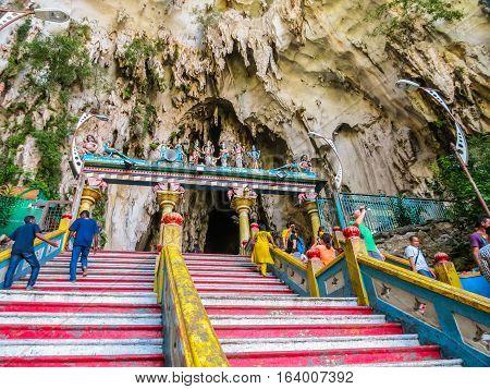 KUALA LUMPUR, MALAYSIA - JANUARY 13, 2014: Pilgrims and visitors go up on a huge ladder to Batu Caves. Kuala Lumpur, Malaysia