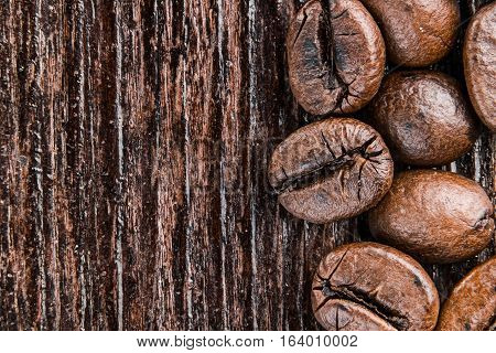 Roasted coffee beans on dark rough wood surface. Super macro view