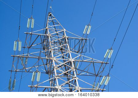 Top section of high-voltage power line metal tower over blue sky