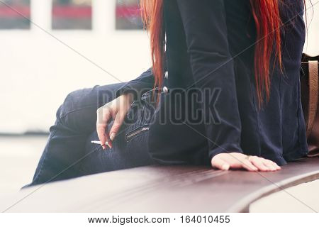 Girl seated on a bench, in a public plaza, is smoking a cigarette.