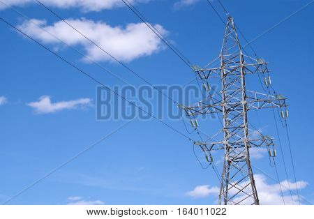 Metal prop and high-voltage power line over blue sky