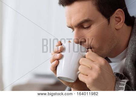 My favourite drink. Handsome nice brunette man holding a cup of tea and drinking at while spending time at home