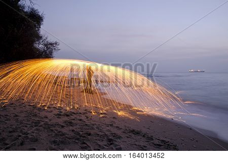 Fire painting, light painting with sparks at winter in seaside