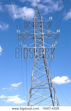 High-voltage power line metal tower over blue sky