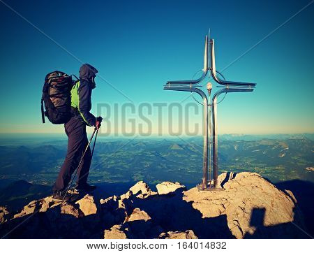 Hiker At Big Crucifix On Mountain Peak. Iron Cross At Alps Mountain Top.