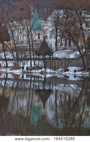 Churches of Sviatohirsk Lavra. Cloudy day in January. Gazebo Chapel on the River