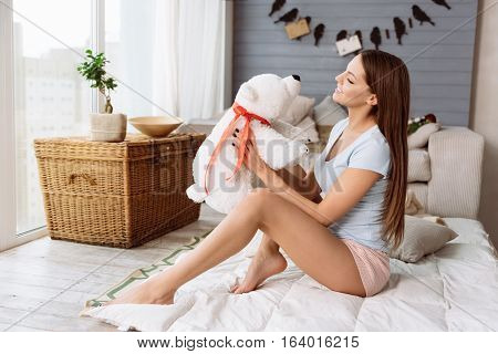 Fluffy toy. Cheerful charming nice woman holding a fluffy bear and looking at it while being in a great mood