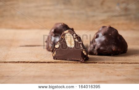 Chocolate candy on wood desk, chocolates with nuts