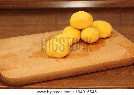 Peeled yellow potatoes on wooden cutting board