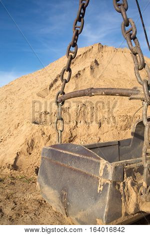 Big heavy bucket against mountain of sand and clear blue sky