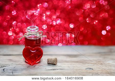 open bottle of love potion transparent red heart on wooden table valentine's day composition