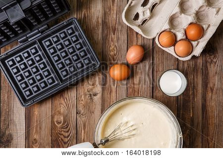 Making waffles at home - waffle iron, batter in bowl and ingredients - milk and eggs. Cooking background.