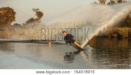Man wakeboarding on a lake. Wakeboarder surfing across the lake.